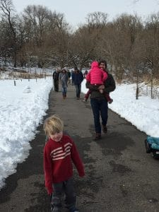 People walk the trail at Tacony Creek Park while the ground is covered in snow.