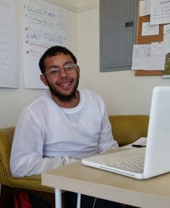 Intern Brayan sits smiling at his desk at TTF
