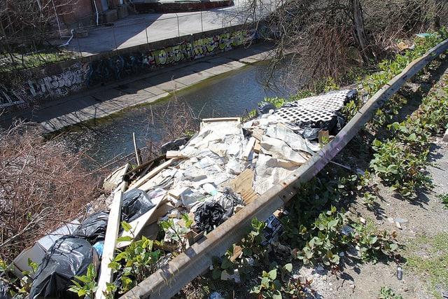Trash dumped alongside a waterway.