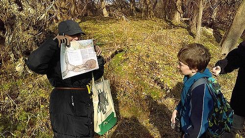 Environmental Educator Judith Gratz holds up educational materials at a nature walk in Tacony Creek Park.
