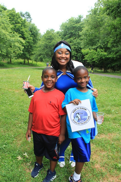 Water Woman stands with two kids at a Tacony Creek Block Party.