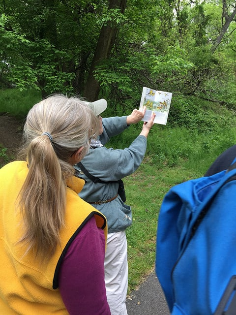 Judith Gratz points to a bird in a bird guide for a group of attendees.