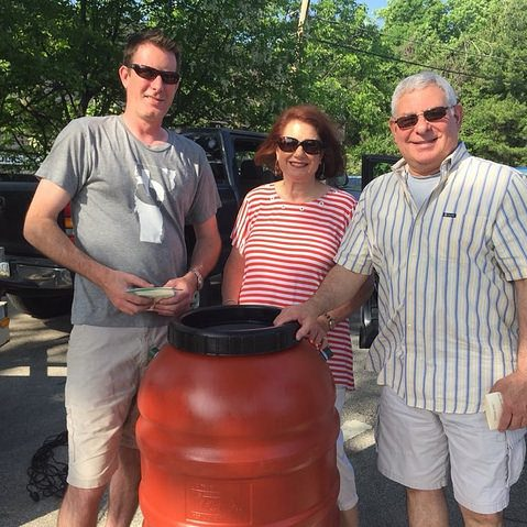 a woman and 2 men with a rain barrel